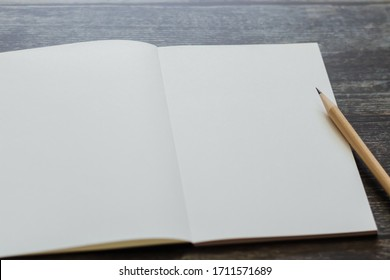 White blank notebook or plain notepd or diary or journal for writing text and message with pencil on old wood table or desk as background with copy space. Still lifestyle photo concept.