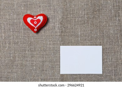 White blank notecard and red handmade heart on textile background