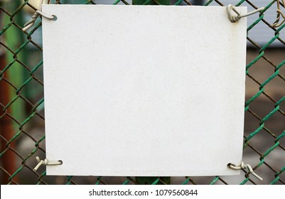 White blank on a mesh fence, paper sheet screwed with wire.