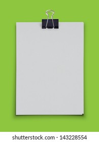 White blank paper with black clip on green background