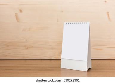 White blank paper desk spiral calendar on wood background.