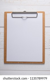 White blank paper on brown clip board on white wooden background, copy space, template