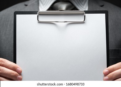 white blank paper sheet closeup in businessman hand, gray suit, dark wall background, blank space for text