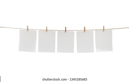 White blank photo cards hanging on clothesline.