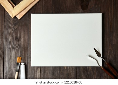 A white blank primed  canvas on stretcher, palette knives, synthetic paintbrush and a tube with oil or acrylic paint lying on a brown wooden table. Top view