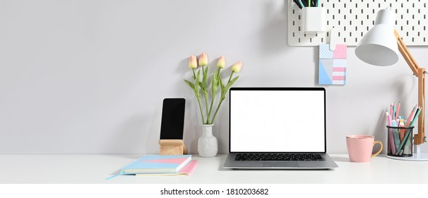 A white blank screen laptop is putting on a white working desk surrounded by various equipment.