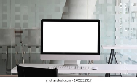 White blank screen monitor putting on white working desk with wireless mouse and keyboard over modern office as background.
