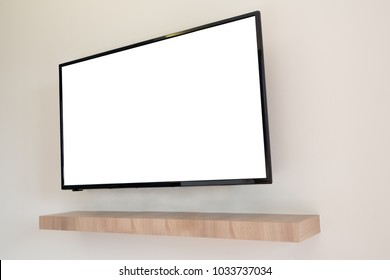white blank screen television on concrete wall at living room with wood shelf. copy space for text on TV. view from side Television