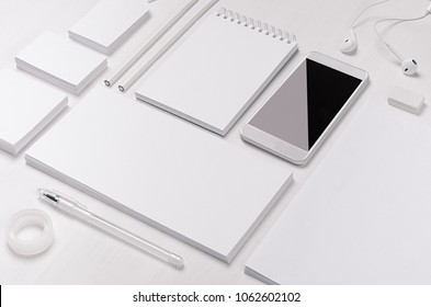 White blank stationery as work place with phone, earphone on light white wood background.