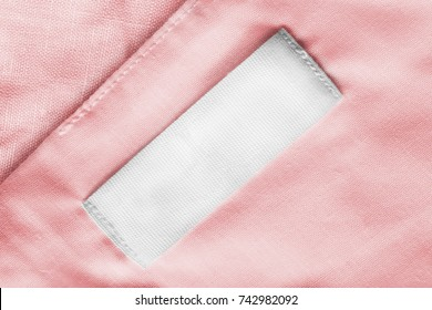 White blank textile clothes label on pink linen as a background