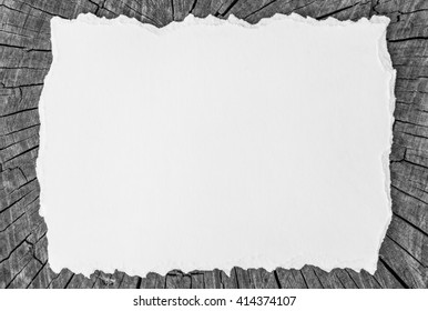 White Blank torn cardboard on the background of a wooden board with cracks, white black picture