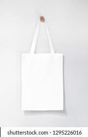 white blank tote bag mock up design on white background hanging on wooden hanger