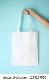 white blank tote bag mock up design on blue background hold by woman hand