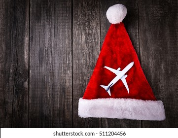 White blank toy of passenger plane on Santa Claus helper hat on rustic wooden background. Christmas and New Year celebration