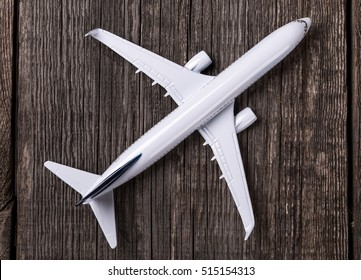 White blank toy of passenger plane on rustic wooden background
