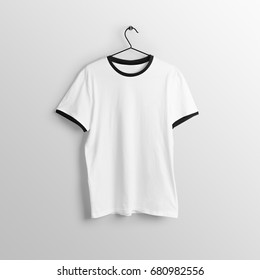 White blank t-shirt mockup on hanger, hanging against empty wall background.