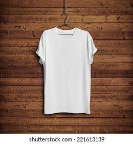 White blank t-shirt on dark wood wall