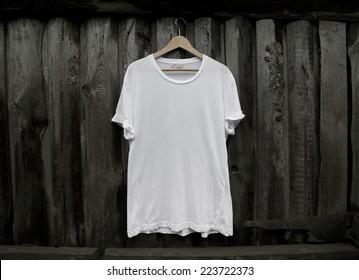 White blank t-shirt on dark wood wall