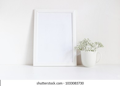 White blank wooden frame mockup with baby breath, Gypsophila flowers in porcelain mug on the table. Poster product design. Styled stock feminine photography. Home decor.