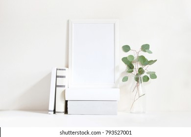 White blank wooden frame mockup with a green eucalyptus branches in glass bottle and pile of books lying on the table. Poster product design. Styled stock feminine photography. Home decor.