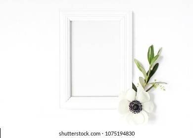 White blank wooden picture frame mockup with green olive branch and anemone flower lying on the white table. Poster product design. Styled stock feminine photography. Home decor. Spring concept.