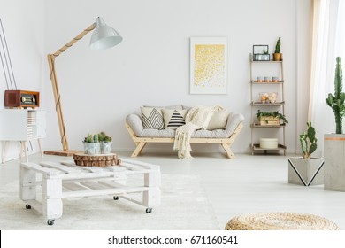White blanket lying on bright wooden couch in a room