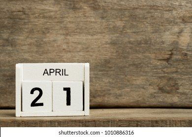 White block calendar present date 21 and month April on wood background