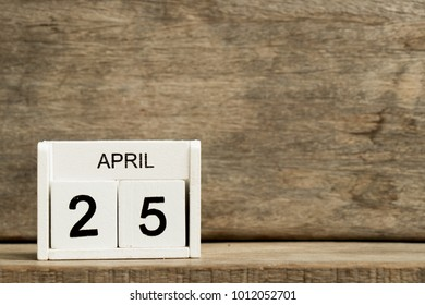 White block calendar present date 25 and month April on wood background