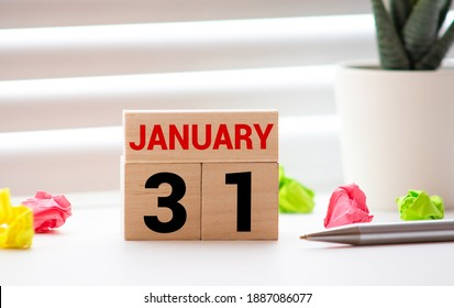 White block calendar present date 31 and month January on wood background.