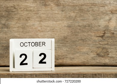 White block calendar present date 22 and month October on wood background (International Stuttering Awareness Day)