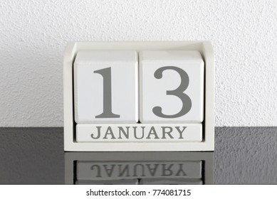 White block calendar present date 13 and month January on white wall background