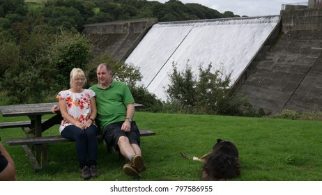 White blonde female sat at a picnic table  in a park with a water weir in the back ground