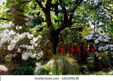 White blossoms of Hymenanthes Hymenathes and jizo (the guardian deity of children)