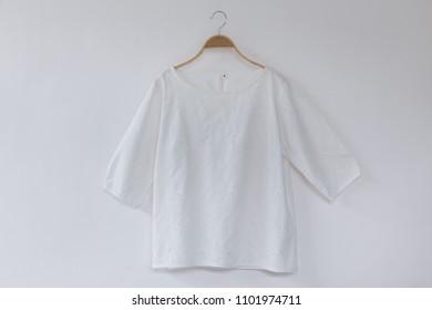 White blouse hanging on white background.