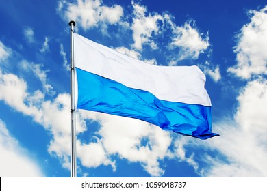 white and blue bavarian flag with blue sky and clouds