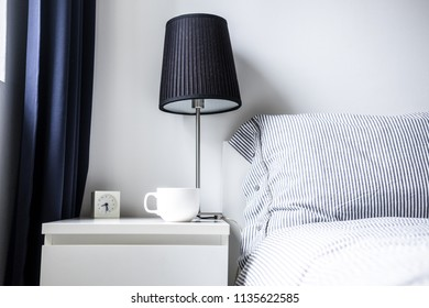 White blue bedroom design ideas. Minimalist comfort style. Night table with lamp, clock, white mug, bed with linen striped pillows and blanket, dark curtain. Copy space