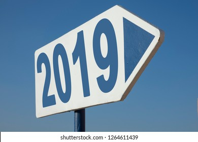white and  blue colored  street sign with an arrow and the word 2019,  business concept for turn of the year and the way to future
