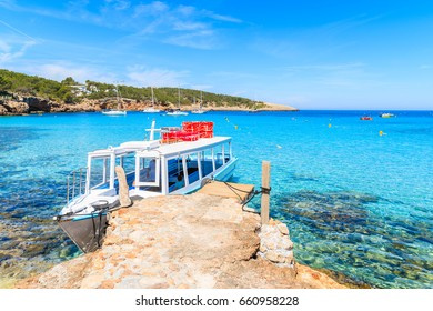 White and blue colour ferry boat for tourists mooring in Cala Portinatx bay, Ibiza island, Spain