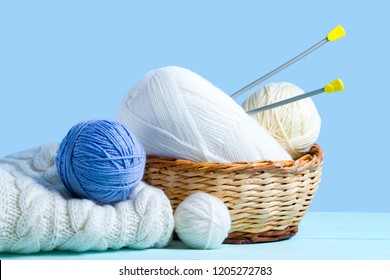 White and blue knitting yarn balls, knitting needles and a white knitted sweater on a blue background. Knitting concept. Knitted and winter clothes