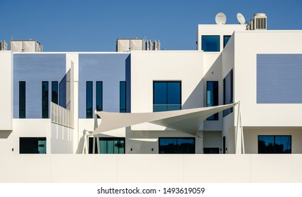 White and blue modern villas in a Middle Eastern, high-end, luxury housing development on a sunny day with strong shadows.