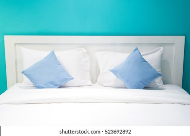 White and blue pillows on a bed Comfortable soft