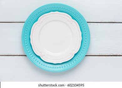 White and blue plates on wooden table. View from above with copy space