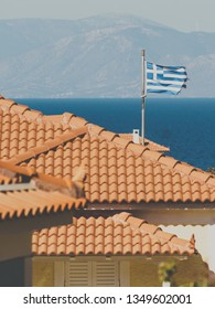 White blue state flag of Greece on roof of private estate, tourist house in seaside Mediterranean town.