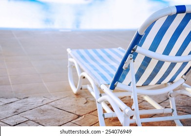 White and blue striped sunbed near swimming pool in holiday resort.
