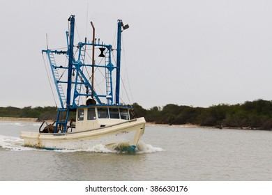 white and blue texas scrimping boat navigating inter-coastal waters