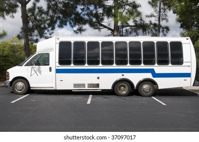 White and Blue Unmarked Shuttle Bus Waiting for Passengers