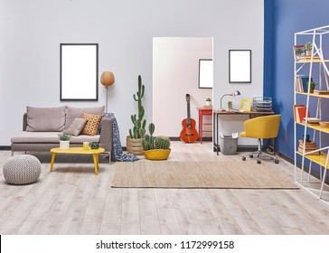 White blue wall concept living room style. Grey sofa and frame decoration. working table in the back and yellow bookshelf.