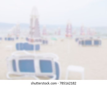 White blur abstract background from tropical beach in sunrise with beach chairs and umbrellas. Sunset on the empty beach in the evening