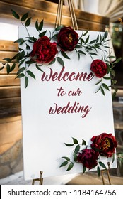 White board decorated with peonies with inscription welcome to our wedding