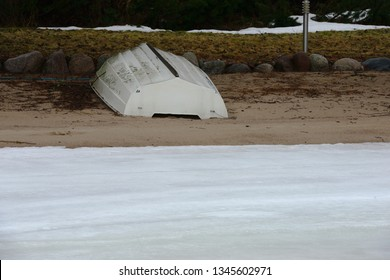 white boat on the beach on the shore of a frozen lake, deadpan photography